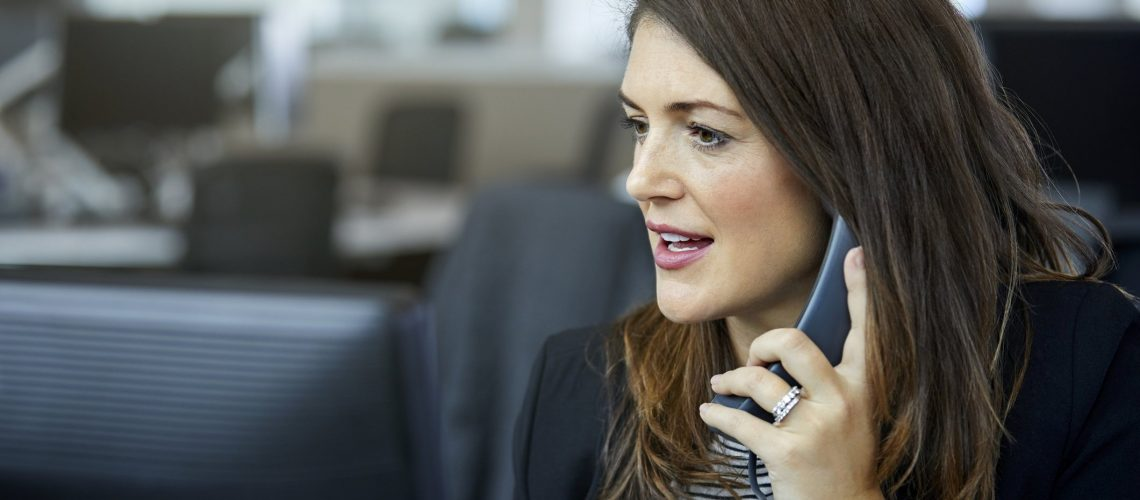 Businesswoman using phone in office. Confident female professional is wearing smart casuals. She is at workplace.